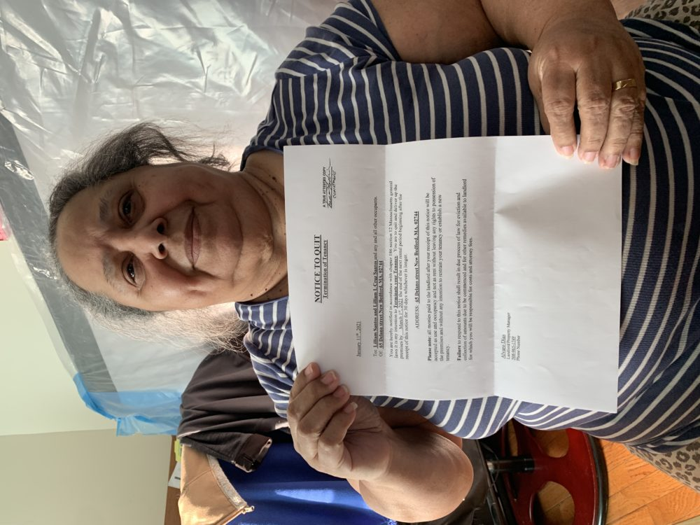 New Bedford resident Liliana Cruz holds up a copy of the eviction letter she received in January. The landlord wants her out by the end of May. (Simón Rios/WBUR)