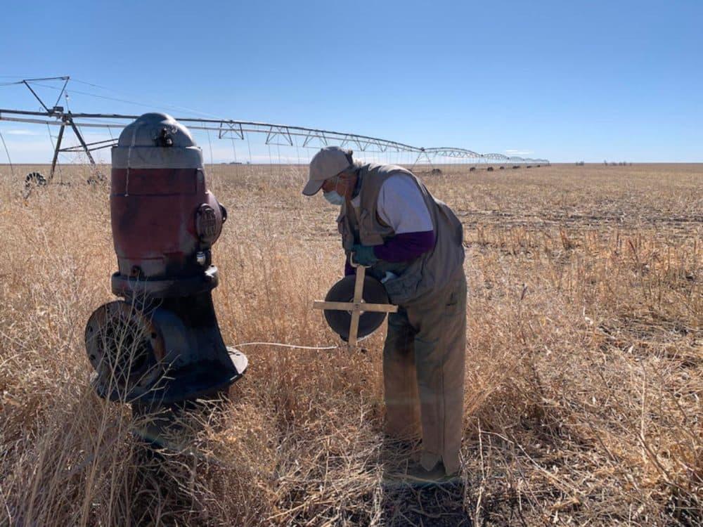 Rex Buchanan of the Kansas Geological Survey measures the aquifer's depth at a well. (David Condos/Kansas News Service)