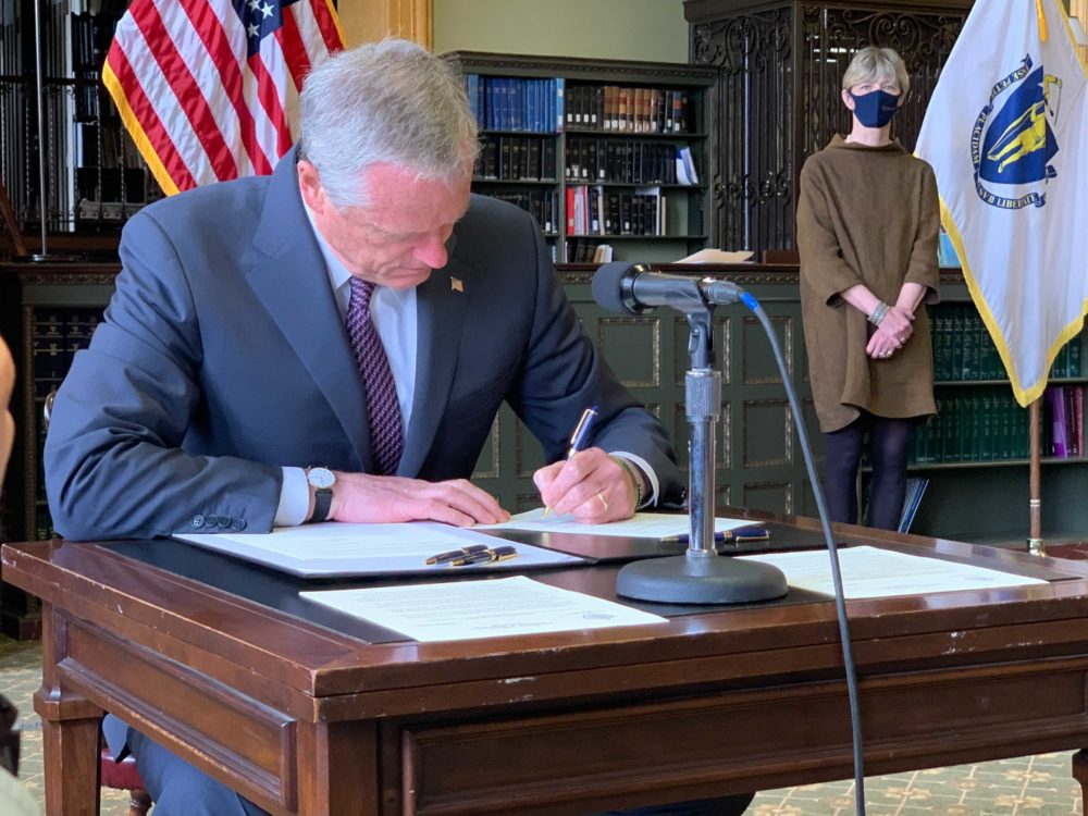 Gov. Charlie Baker signs an order ending the state of emergency put in place during the COVID-19 pandemic. (Steve Brown/WBUR)