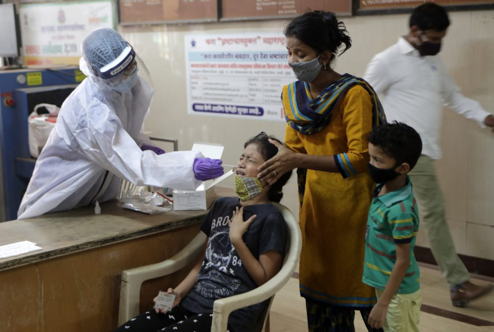 A girl reacts as a health worker collects her swab sample to test for COVID-19 in Mumbai, India, Tuesday, April 20, 2021. (Rajanish Kakade/AP)