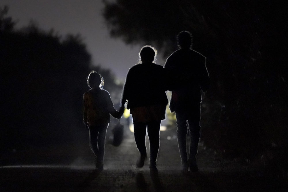 A 7-year-old migrant girl from Honduras, left, walks with Fernanda Solis, 25, center, also of Honduras, and an unidentified man. They're approaching a U.S. Customs and Border Protection processing center to turn themselves in while seeking asylum, moments after crossing the U.S.-Mexico border in Mission, Texas. (Julio Cortez/AP)