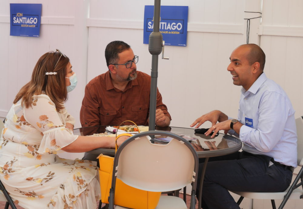 State Rep. Jon Santiago (right) makes his pitch to become Boston's first Latino mayor at a campaign event in East Boston on May 16.  He is pictured talking with two attendees, Luz Arango and Juan Bonilla. (Courtesy of Santiago's campaign) (courtesy of the campaign)