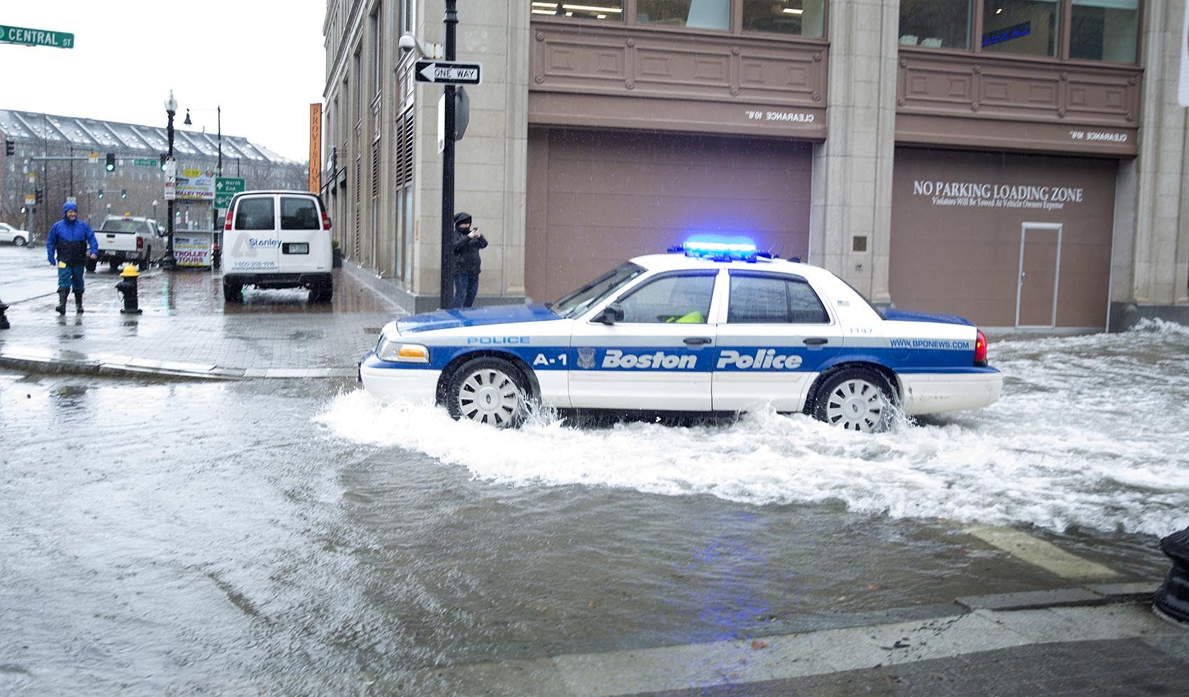 A police car navigates through floodwaters on Central St. to reach Atlantic Ave. (Robin Lubbock/WBUR)