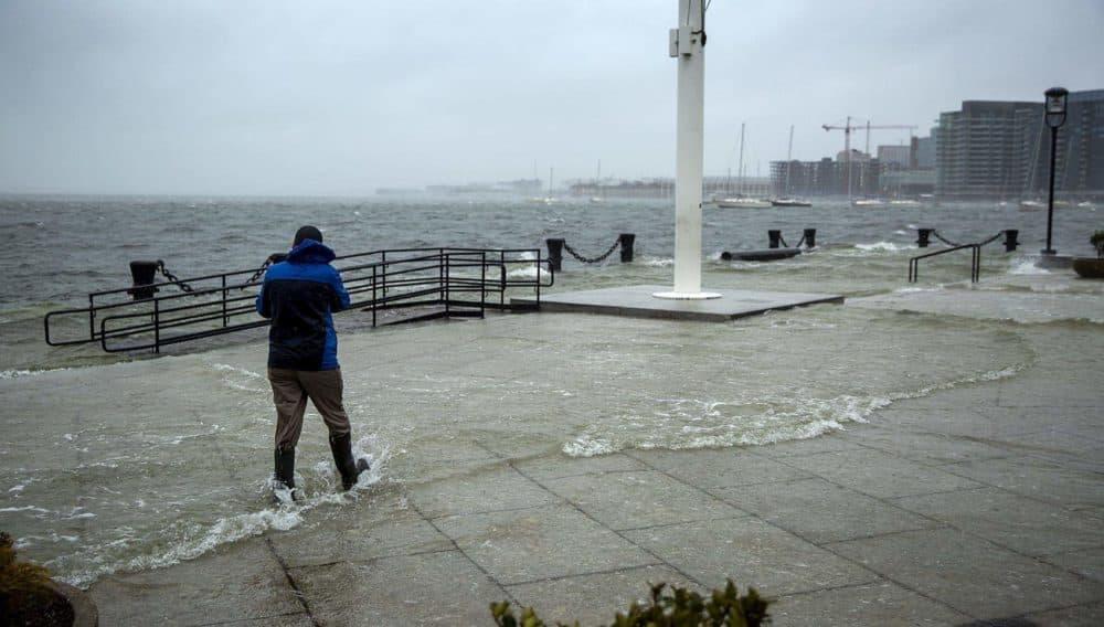 man walking through flood waters at Long Wharf, Boston, U.S.A. | photo credit Robin Lubbock, W-B-U-R