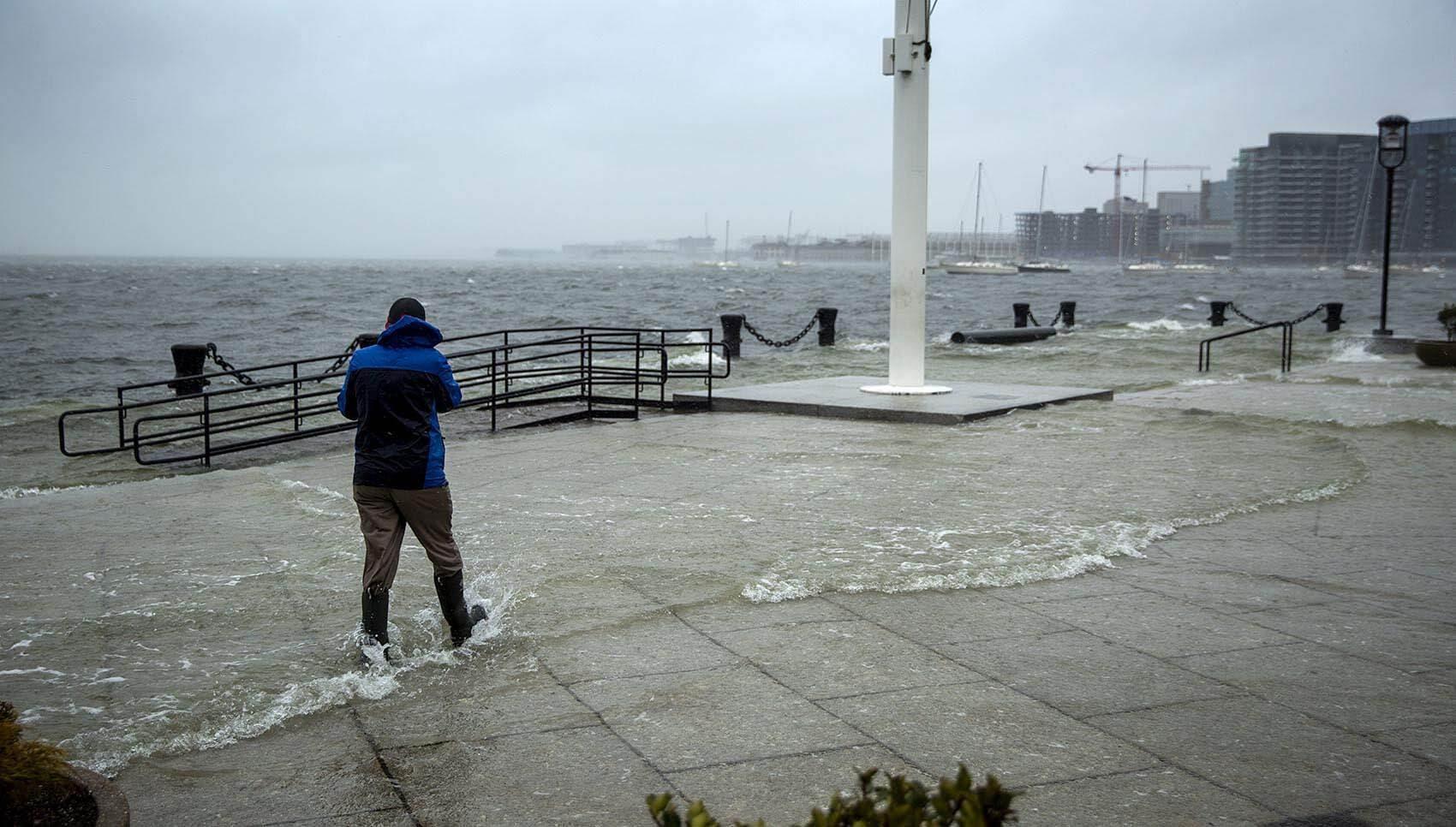 A man walks through water flooding over Long Wharf in Boston. (Robin Lubbock/WBUR)