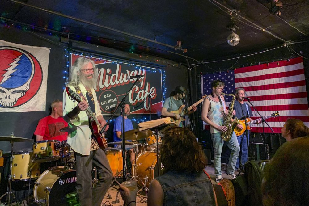 """The Mystical Misfits perform with guest drummer """"Uncle Johnny"""" Frazee during the Hippie Hour at the Midway Cafe on the 10th anniversary of the popular weekly Grateful Dead residency. (Amelia Mason/WBUR)"""