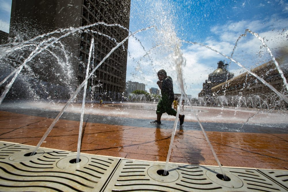 Tracy Thibodeaux, 5, cools off in the fountain at the Christian Science Plaza on a hot 94º day. (Jesse Costa/WBUR)