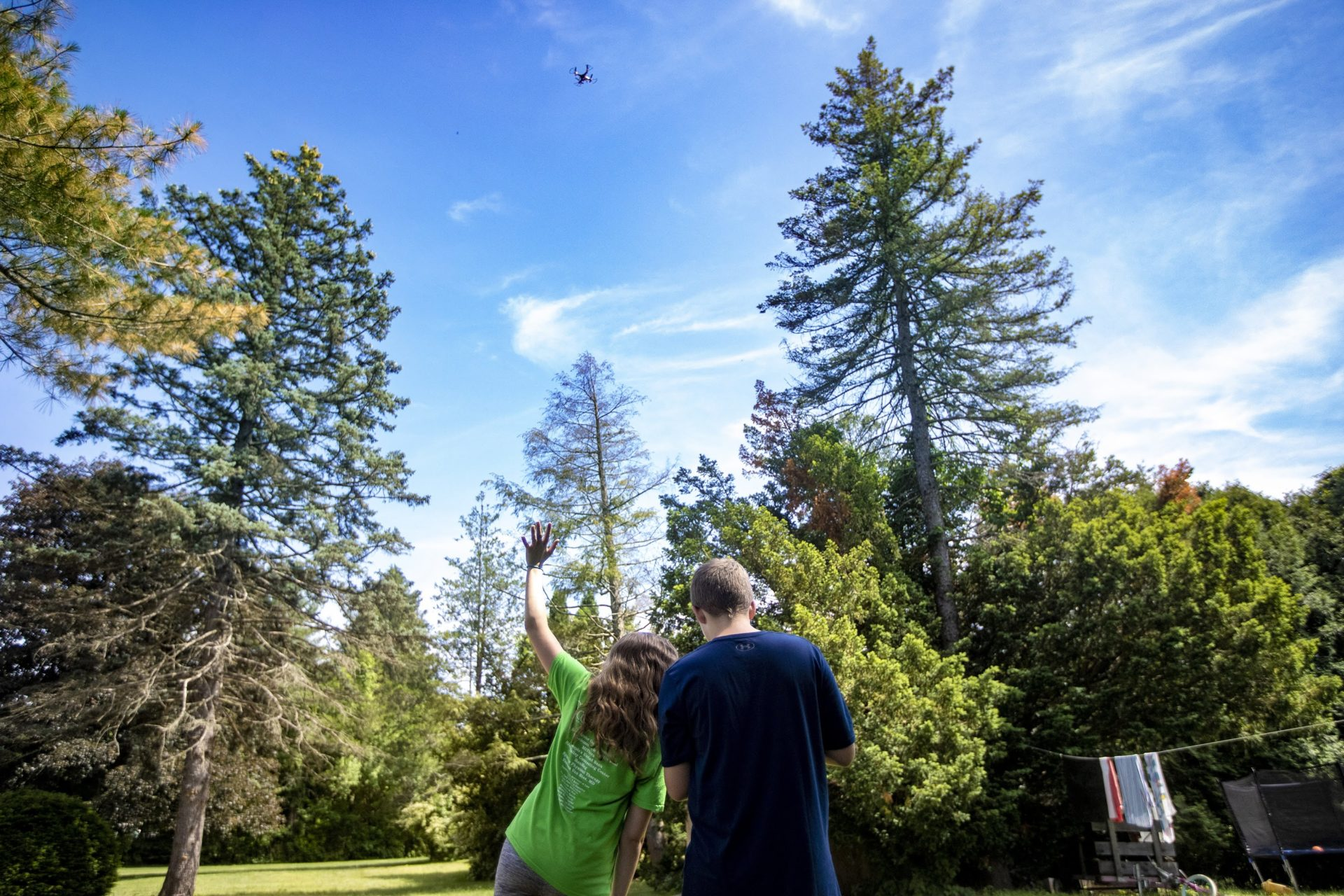 Emily, 13, waves at the drone that her brother Charlie, 12, is flying high above their heads in the backyard of their home in West Springfield. (Jesse Costa/WBUR)