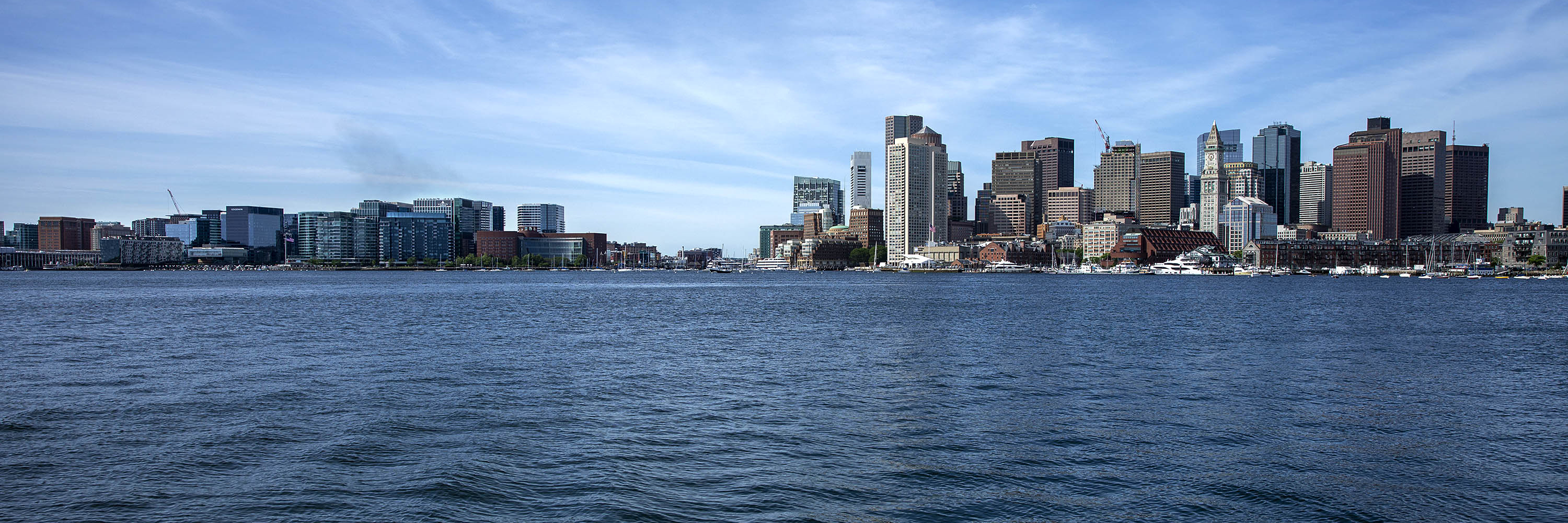 The Boston skyline seen from across the harbor with the Seaport on the left, central Boston on the right and Fort Point channel running between the two. (Robin Lubbock/WBUR)