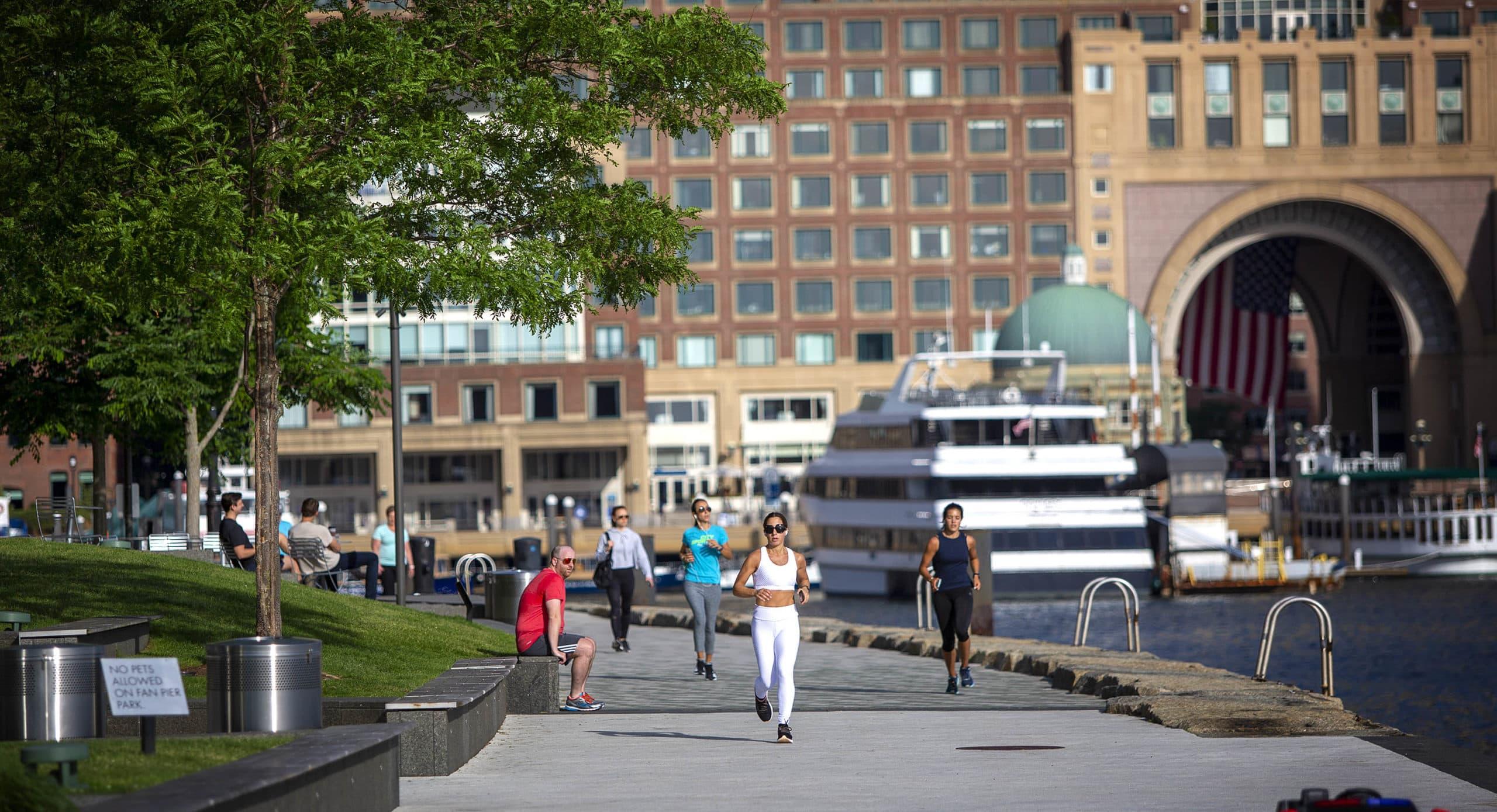 Joggers take advantage of a recent warm day as they run along the Harborwalk at Fan Pier. (Robin Lubbock/WBUR)