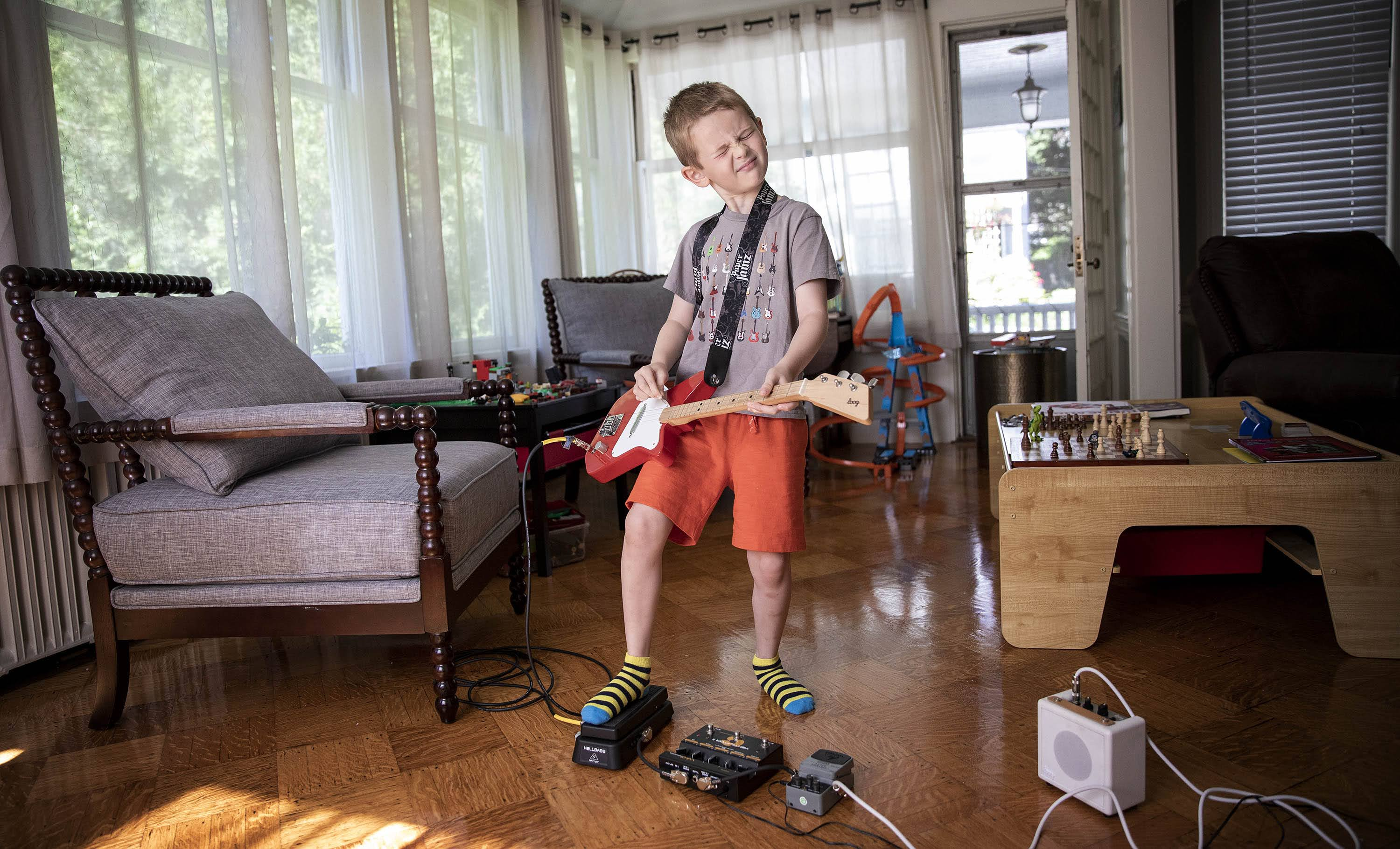 """Arlen gets in some practice on his electric guitar.  The young musician is the inspiration for """"The Boy Who Wanted to Rock,"""" written by his father Dave Weiser. (Robin Lubbock/WBUR)"""
