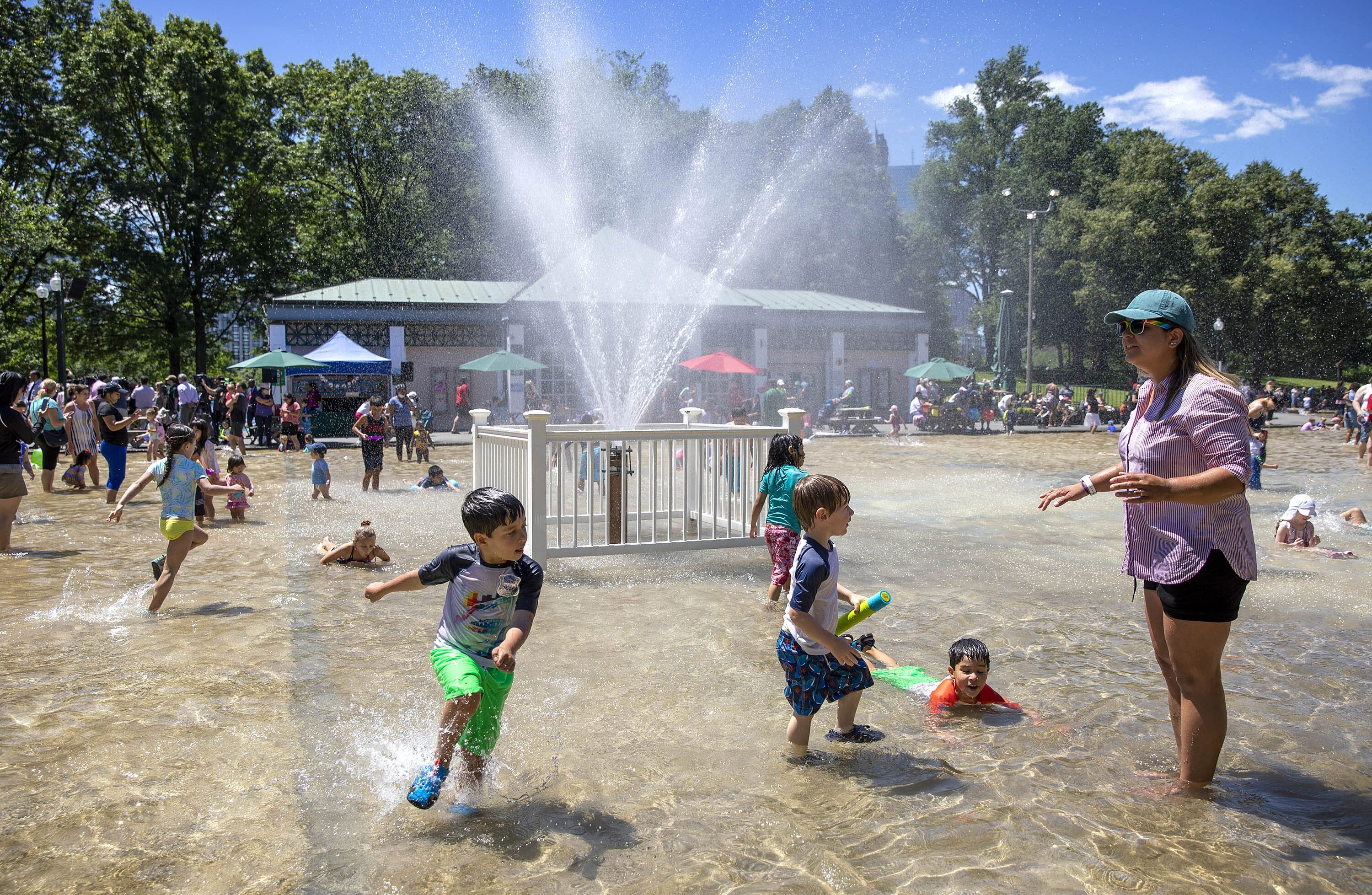 Children splash through the water by the fountain at the summer opening of Boston's Frog Pond. (Robin Lubbock/WBUR)