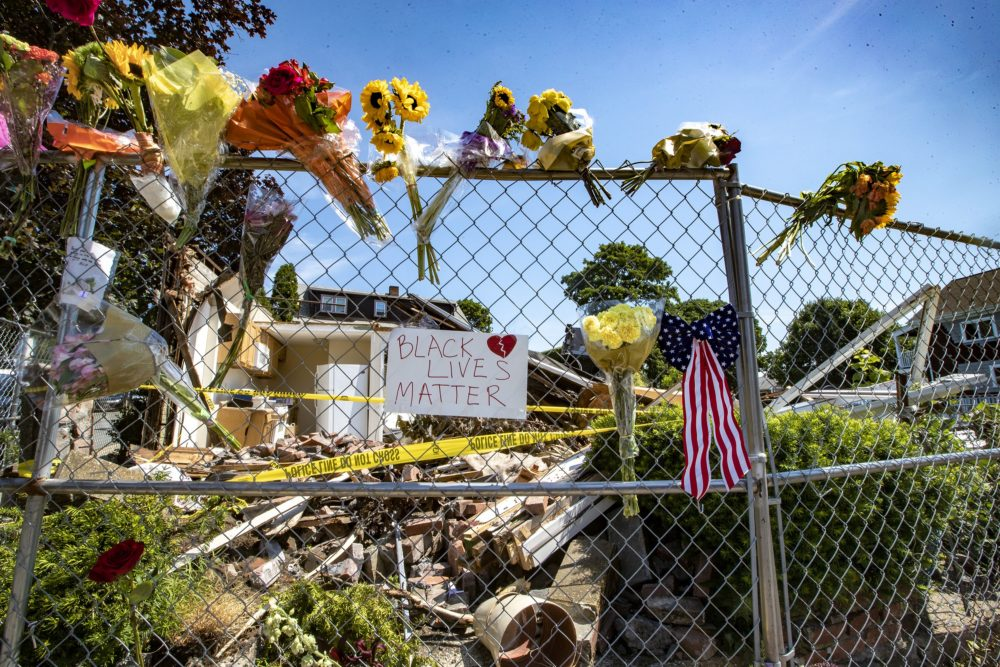 Flowers are seen near where a gunman killed two people after crashing a stolen truck on Saturday in Winthrop. (Jesse Costa/WBUR)