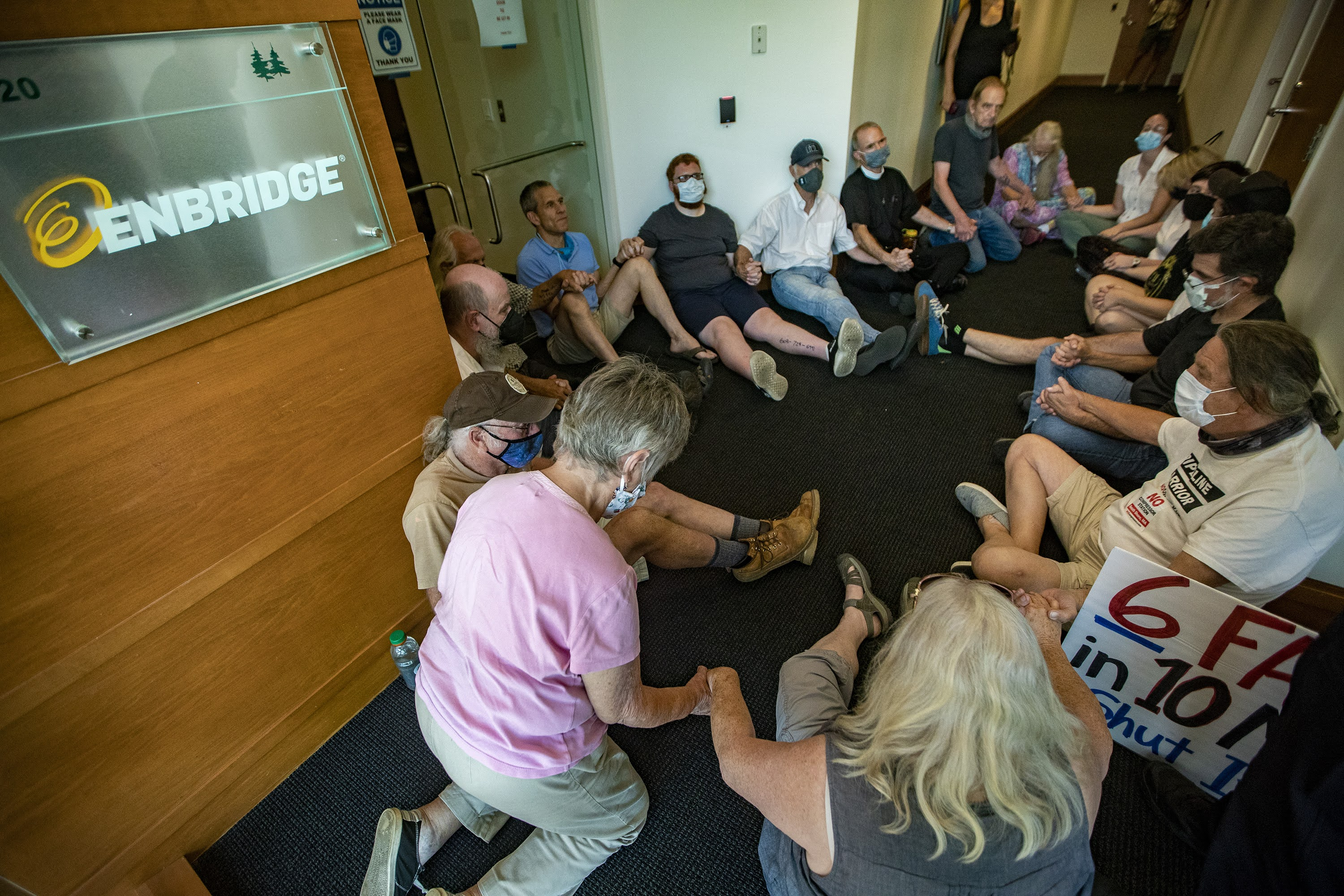 A group of protesters gather near the front door of the Enbridge office in Waltham. (Jesse Costa/WBUR)
