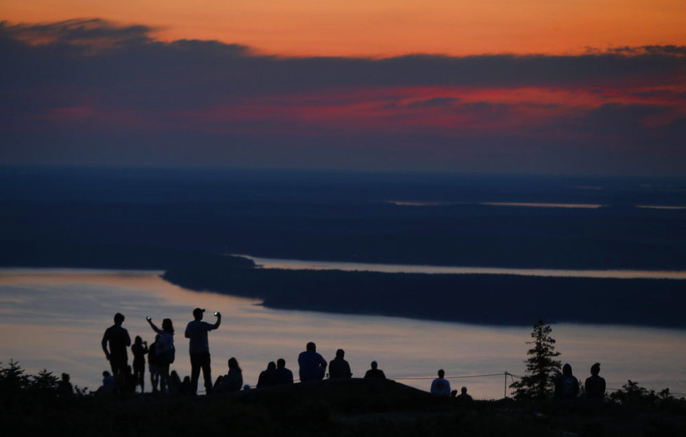 A crowd gathers near the summit of Cadillac Mountain in Acadia National Park. (Robert F. Bukaty/AP Photo)