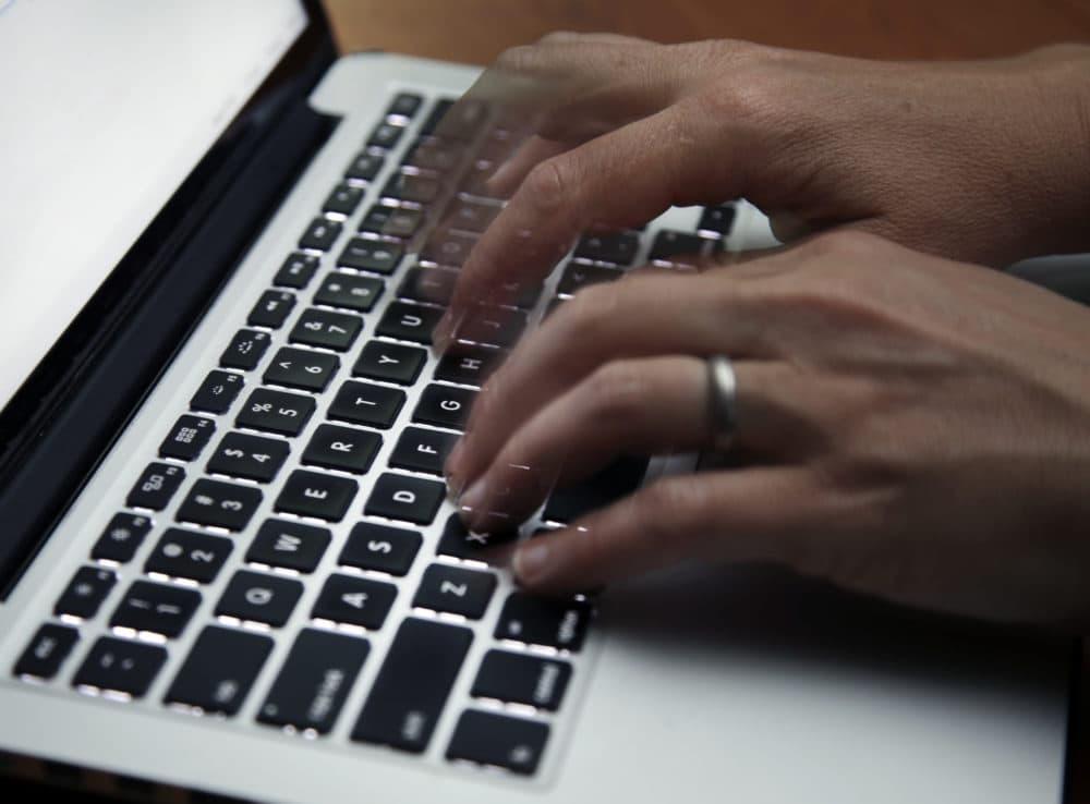 A person working on a laptop. (Elise Amendola/AP)