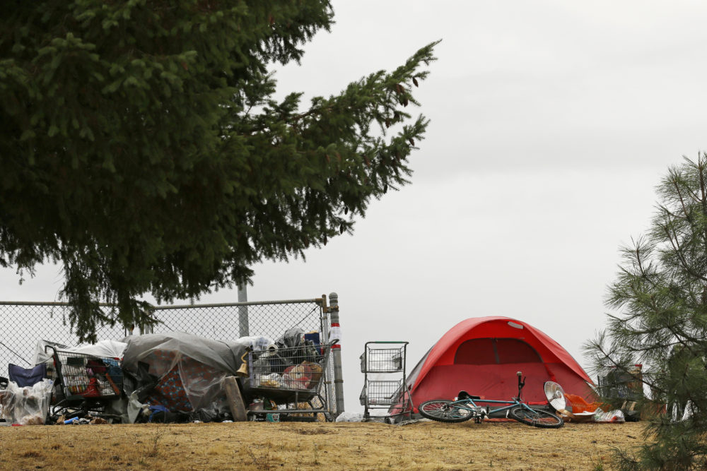 A tent and shopping carts filled with belongings are near a neighborhood in Portland, Ore. (Ted S. Warren/AP/File)