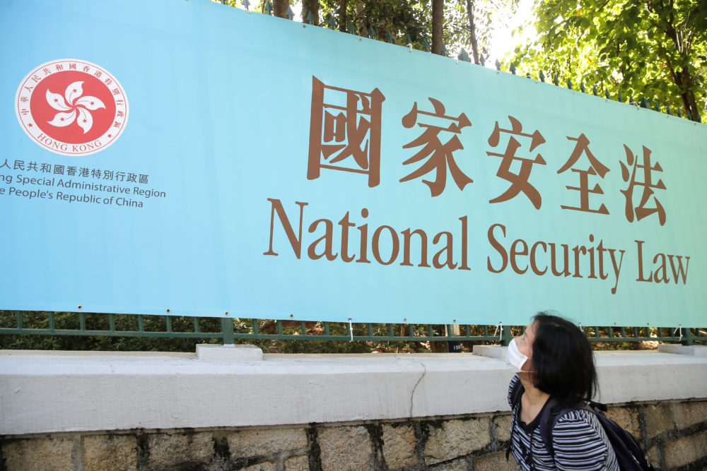A woman walks past a promotional banner of the China's national security law in Hong Kong on June 30, 2020. (Kin Cheung/AP)