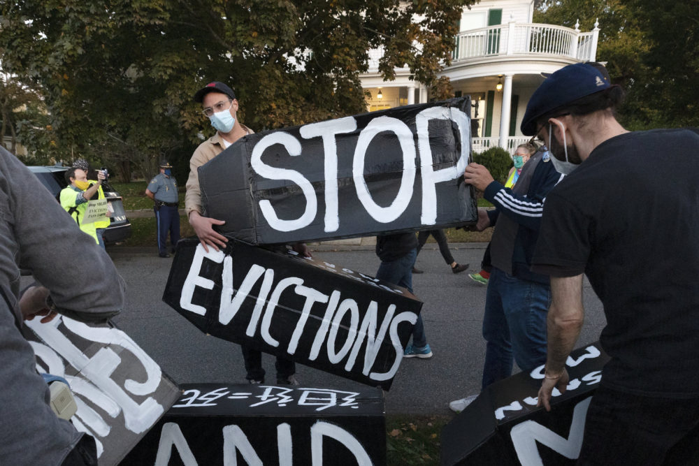 In this Oct. 14, 2020, file photo, housing activists erect a sign in front of Massachusetts Gov. Charlie Baker's house in Swampscott, Mass. (Michael Dwyer/AP File)