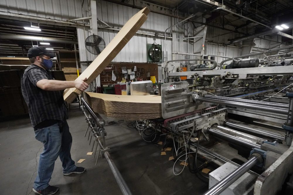 Rob Bondurant, a supervisor at Great Southern Industries, a packaging company, loads up a finishing machine in the Jackson, Miss., facility, May 28, 2021. The lack of workers has forced some supervisors to assume additional duties. (Rogelio V. Solis/AP)