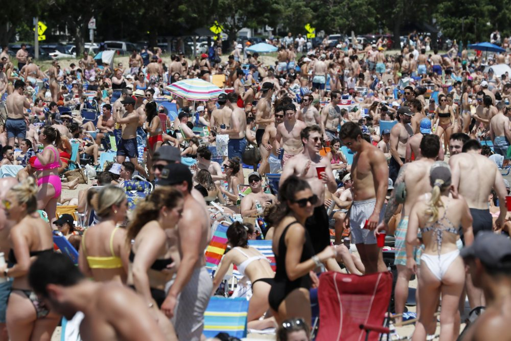 Crowds gather on L Street Beach on Saturday, June 5 in South Boston. New England has among the highest vaccination rates in the U.S. and is seeing sustained drops in COVID-19 cases, hospitalizations and deaths. (Michael Dwyer/AP)