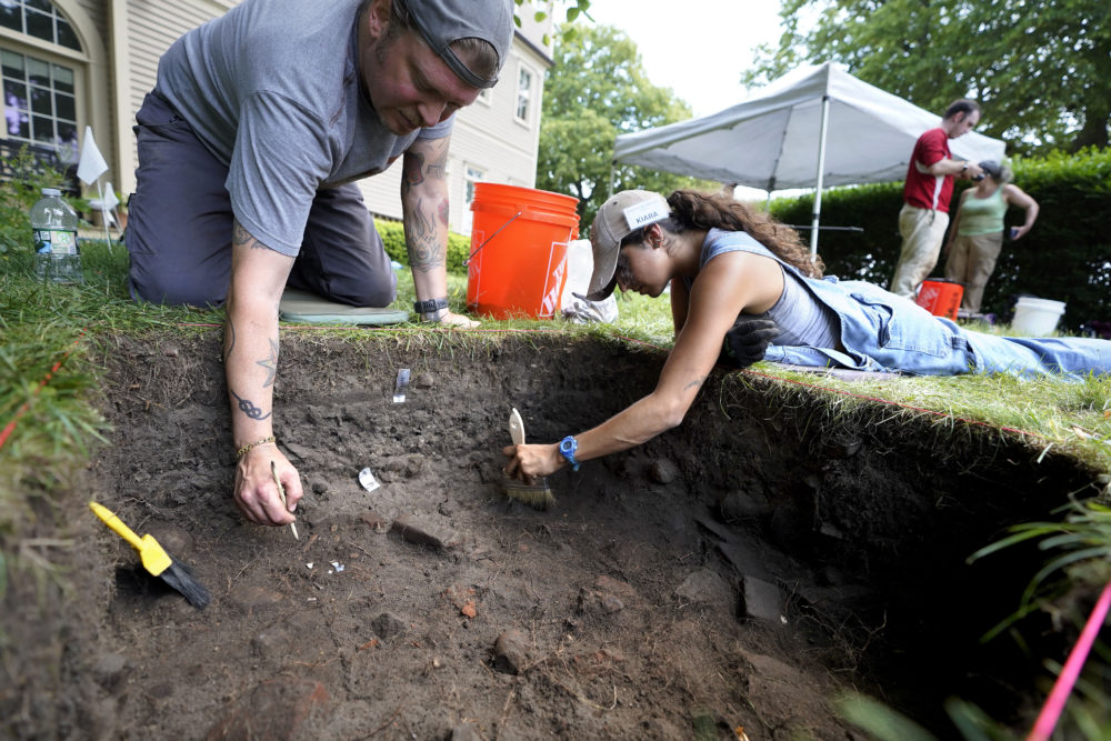 UMass Boston graduate students Nicholas Densley and Kiara Montes use brushes while searching for artifacts at the excavation site on Wednesday on Cole's Hill, in Plymouth. (Steven Senne/AP)