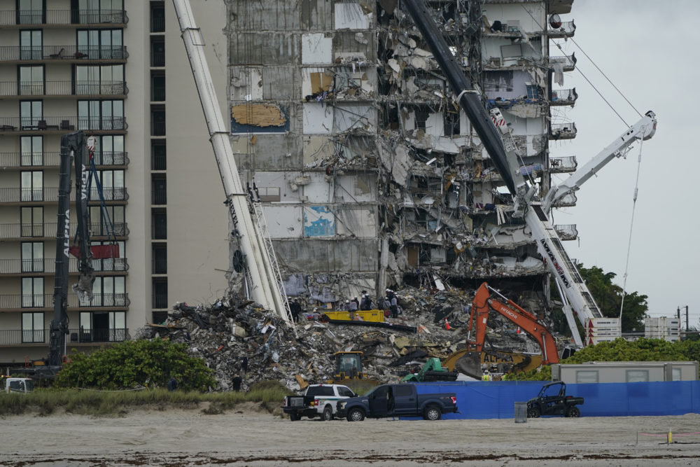 June 30, 2021: Search and rescue personnel work alongside heavy machinery to sift through the rubble at the Champlain Towers South condo building, where scores of people remain missing almost a week after it partially collapsed in Surfside, Fla. (Lynne Sladky/AP)