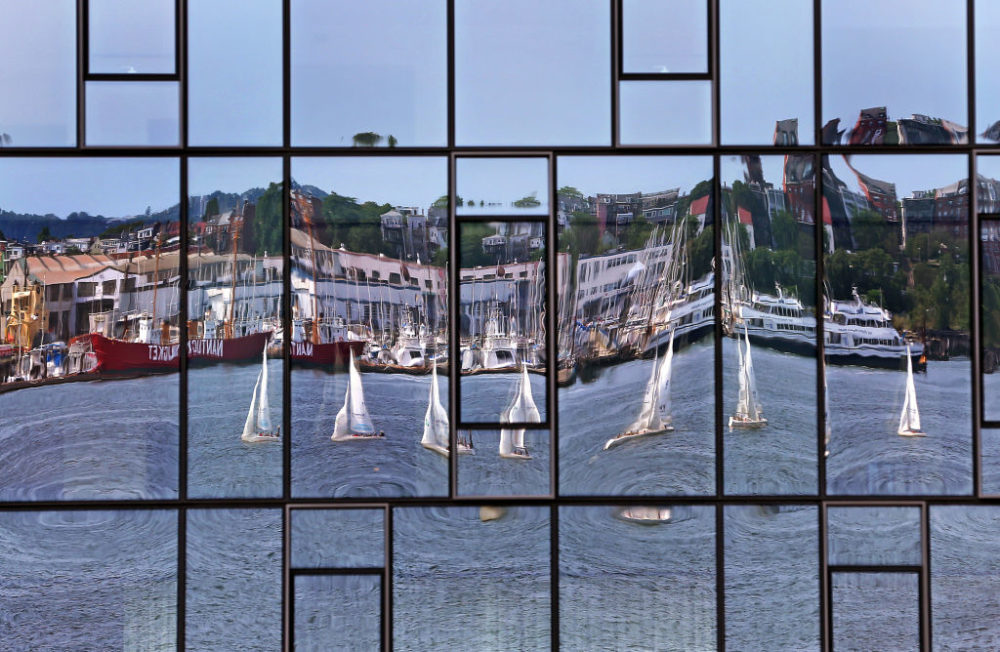 The glass of the Residences at Pier 4 Boston condominium complex in the Seaport neighborhood of Boston reflected sailboats on Boston Harbor on Aug. 14, 2019. (David L. Ryan/The Boston Globe via Getty Images)