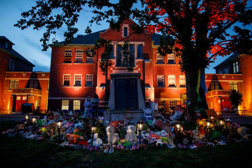A makeshift memorial to honor the 215 children whose remains have been discovered buried near the facility is seen as orange light drapes the facade of the former Kamloops Indian Residential School in Kamloops, British Columbia, Canada, on June 2, 2021. (Cole Burston/AFP/Getty Images)