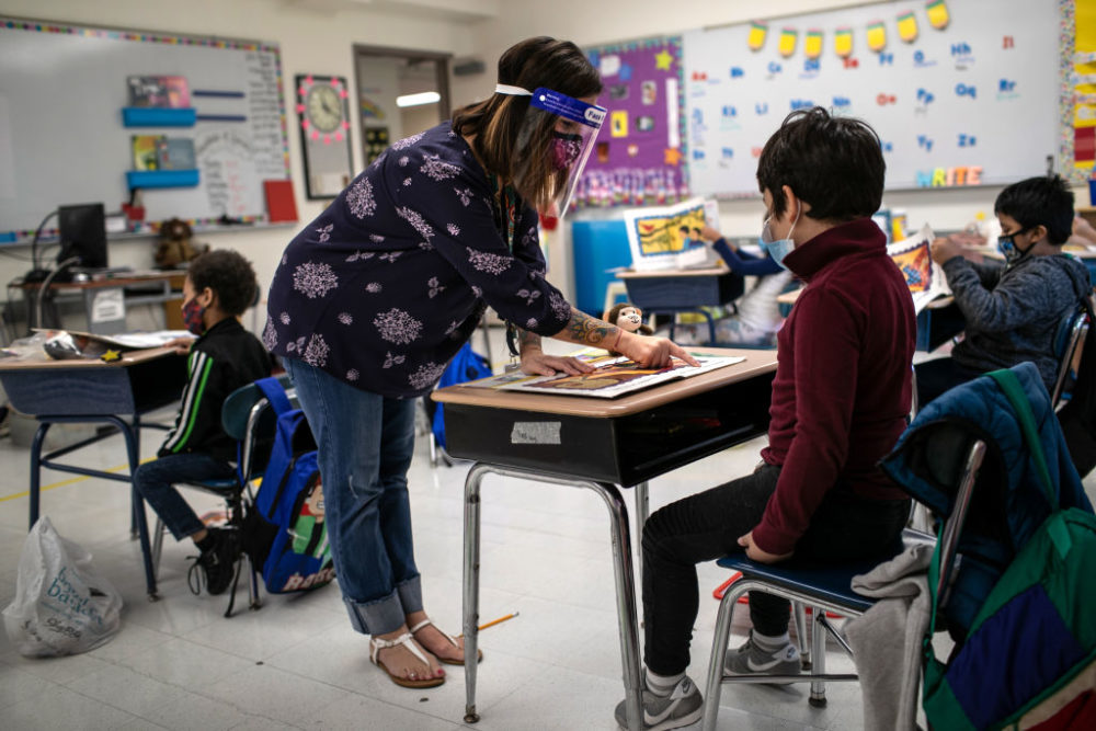 Teacher Elizabeth DeSantis, wearing a mask and face shield, helps a first grader during reading class at Stark Elementary School on September 16, 2020 in Stamford, Connecticut. Most students at Stamford Public Schools are taking part in a hybrid education model, where they attend in-school classes every other day and distance learn the rest. About 20 percent of students in the school district, however, are enrolled in the distance learning option due to coronavirus concerns. (Photo by John Moore/Getty Images)