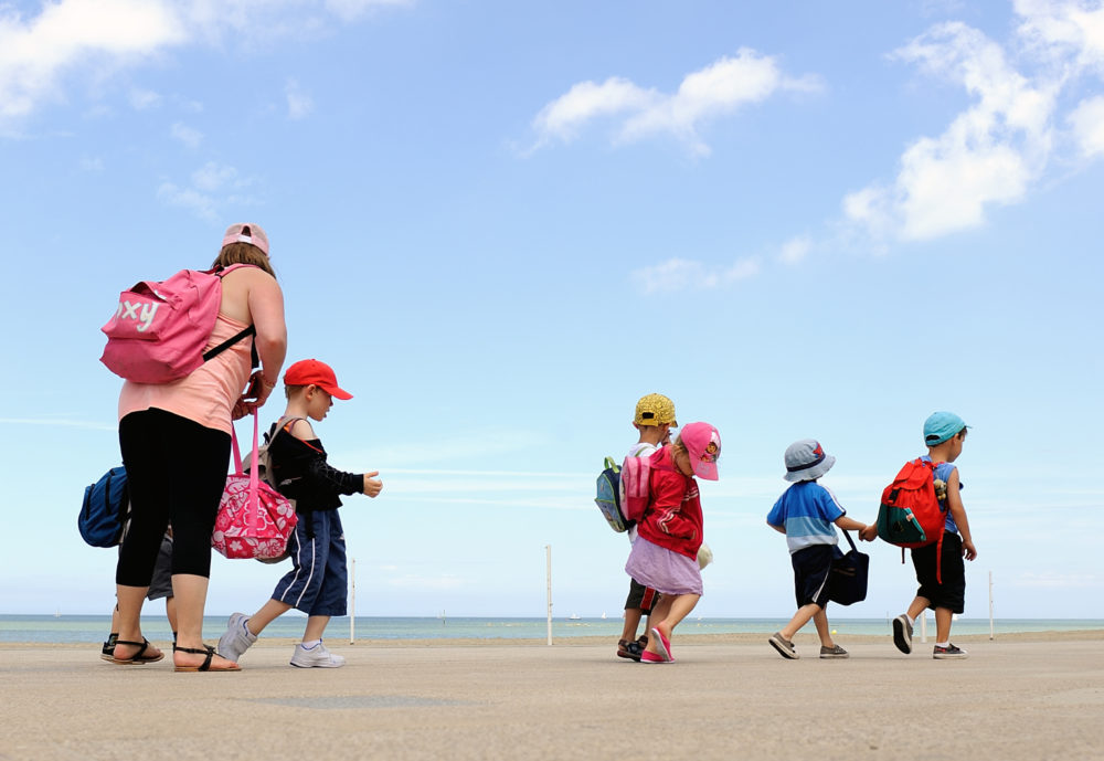 A summer camp monitor looks after children (Philippe Huguen/AFP via Getty Images)