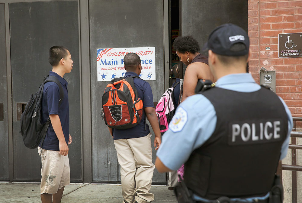 A probationary Chicago police officer watches as students arrive at Laura Ward Elementary School in Chicago, Illinois. (Scott Olson/Getty Images)