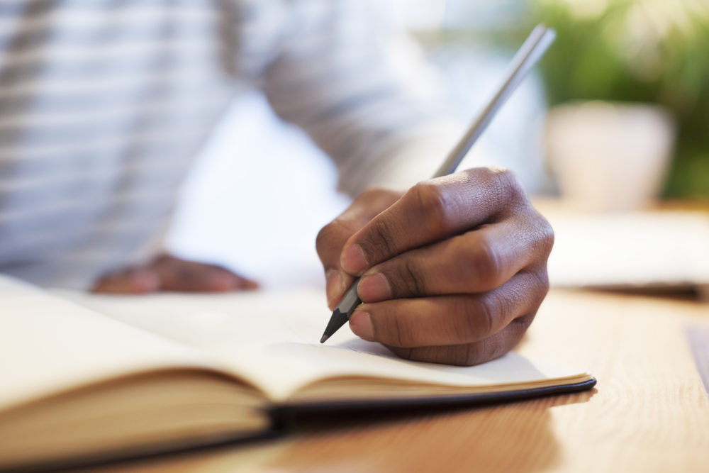 Man's hand drawing in a notebook (Getty Images)