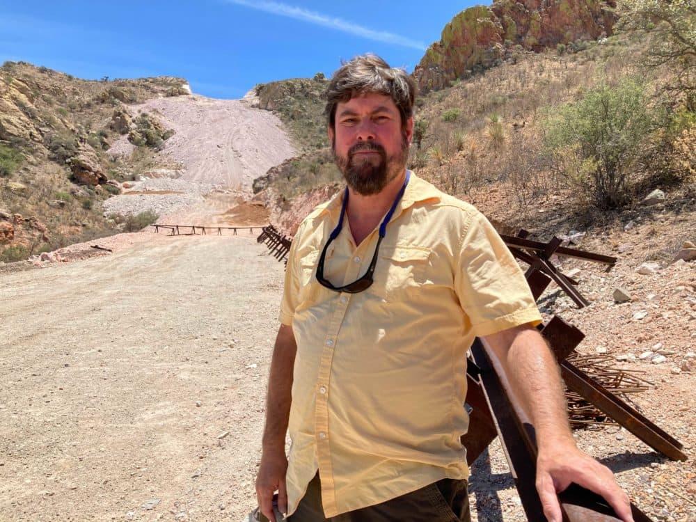 Miles Trafagan de Wildlands Network filmado frente a la cima de una montaña que explota y conduce al muro fronterizo, inacabado e inseguro.  (Peter O Dowd / Aquí y ahora)