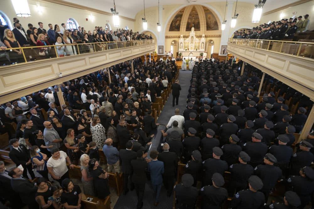 WORCESTER - The casket of fallen Worcester Police Officer Enmanuel Familia is escorted into his funeral Mass at St. John Church in Worcester, Massachusetts Thursday, June 10, 2021. ASHLEY GREEN / TELEGRAM & GAZETTE