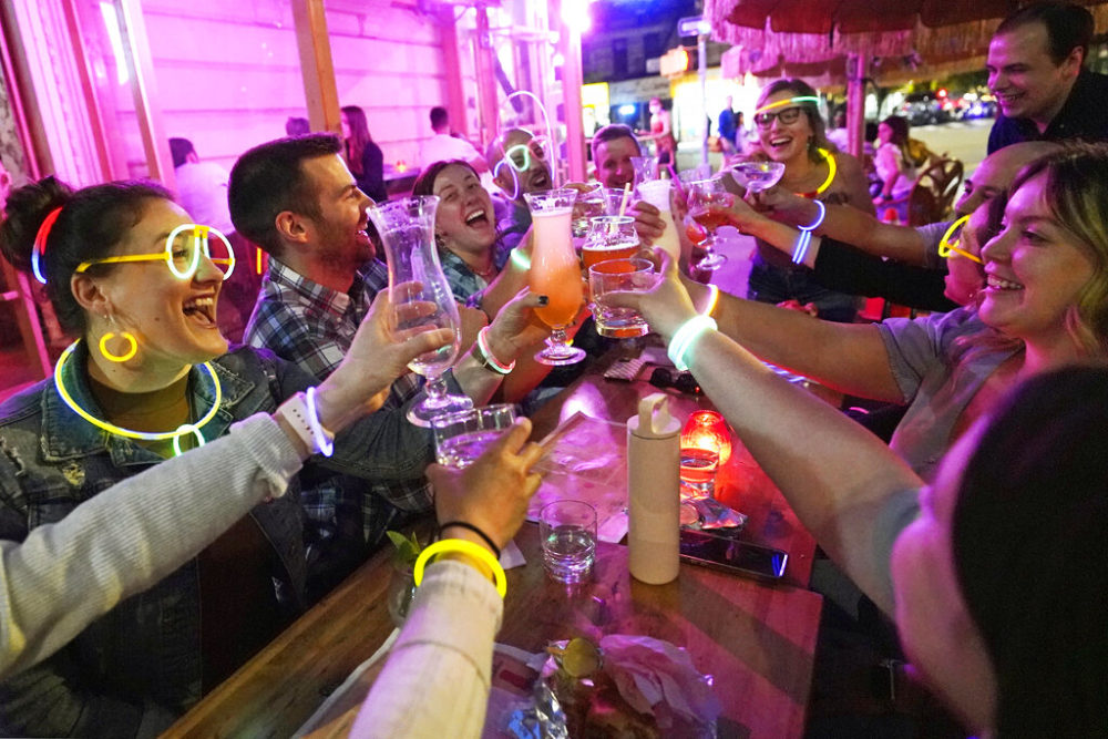 Emily Baumgartner, left, and Luke Finley, second from left, join friends in a birthday toast at the Tiki Bar on Manhattan's Upper West Side Monday, May 17, 2021, in New York. Restaurants, shops, gyms and many other businesses in New York can go back to full occupancy if all patrons are inoculated. (Kathy Willens/AP)