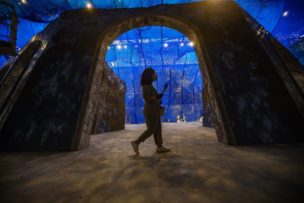 Firelei Báez walks with a brush and paint can in hand as she works on her largest sculptural installation to date, a reimagined version of the archeological ruins of the Sans-Souci Palace in Haiti installed at the ICA Watershed in East Boston. (Jesse Costa/WBUR)