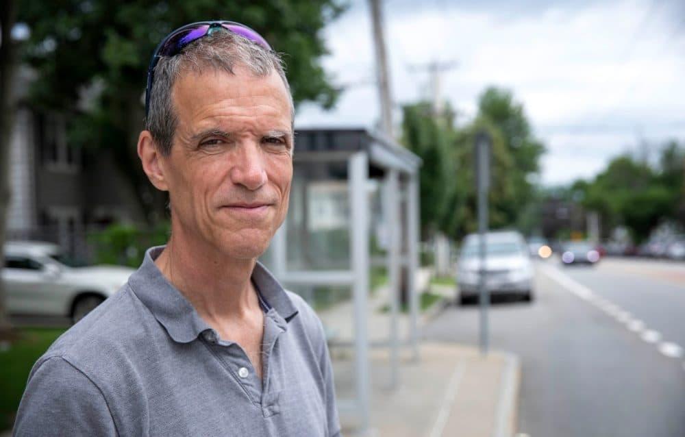 El senador estatal Will Brownsberger parado en una parada de autobús en Belmont.  (Robin Lubbock / WBUR)