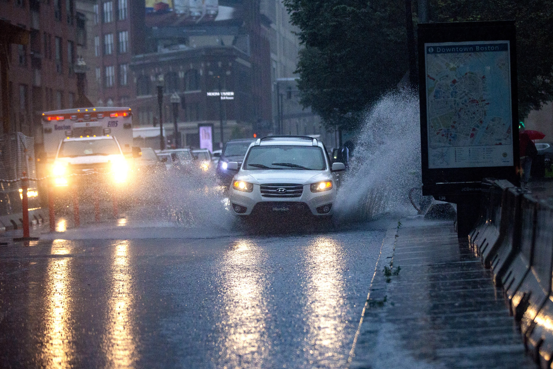 Cars drive through a flooded Stuart Street during the heavy rain from Tropical Storm Elsa. (Jesse Costa/WBUR)