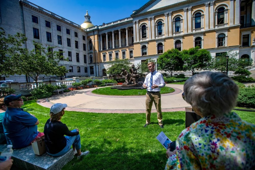 A small group of State House tour participants sit in the shade during a hot sunny day  as they listen to Suffolk University. senior Alex Svenson explain the origin of the Massachusetts Firefighters Memorial behind him. (Jesse Costa/WBUR)