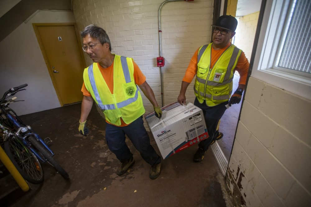 Chelsea Public Works staff Wai Leong and Cesar Cortez deliver a window air conditioner unit to a resident at the Prattville Apartments public development in Chelsea. (Jesse Costa/WBUR)