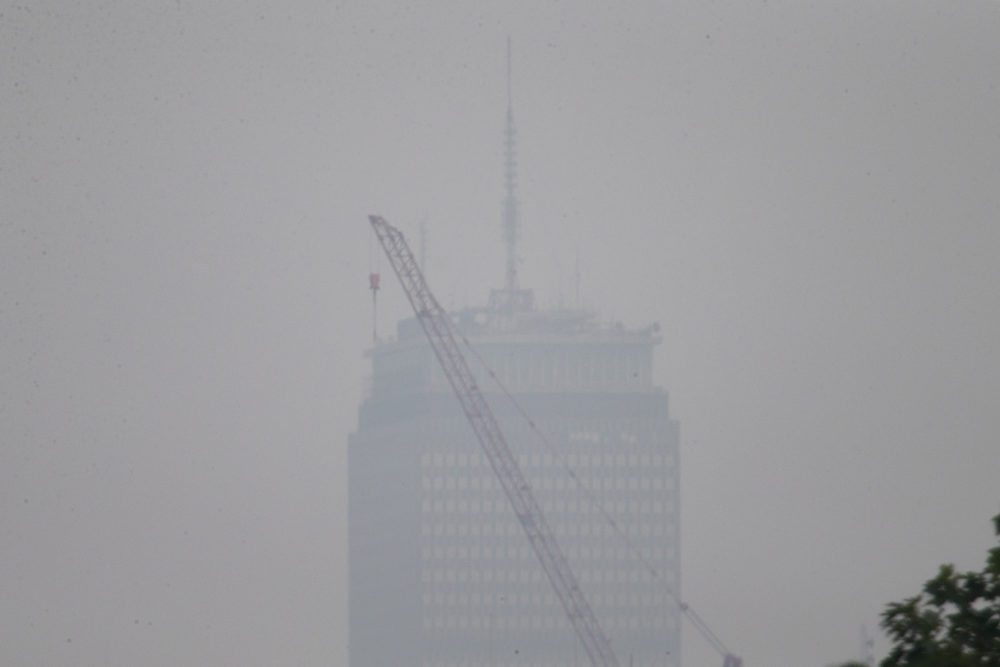 A view of the Prudential Tower from Somerville on Monday afternoon. Smoke from the wildfires from the western part of the country and Canada returned to Boston. (Jesse Costa/WBUR)