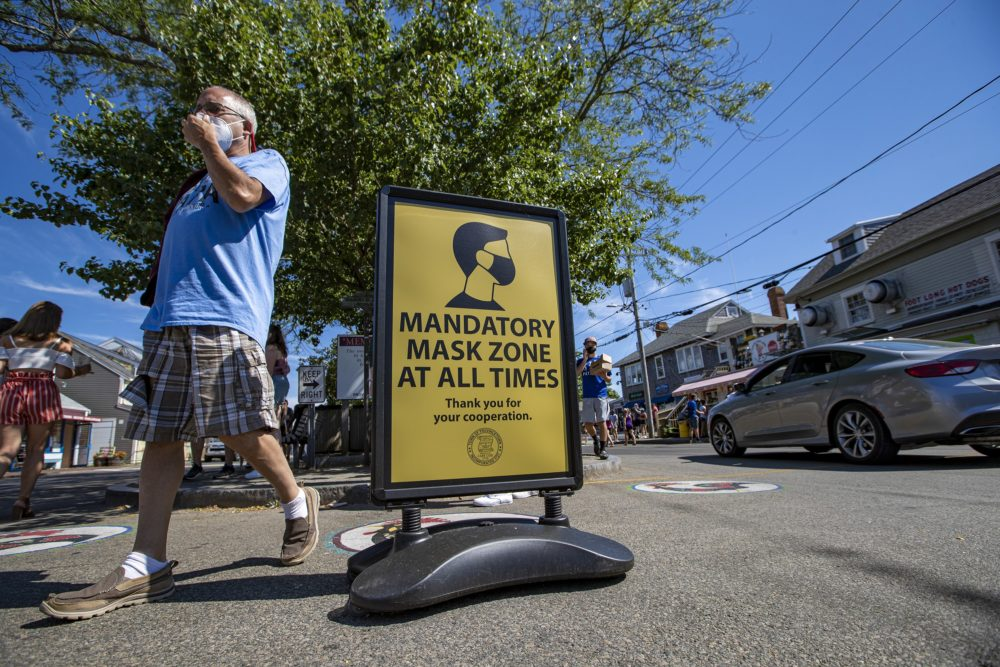 A man adjusts his mask as he walks across Commercial Street in Provincetown. (Jesse Costa/WBUR)