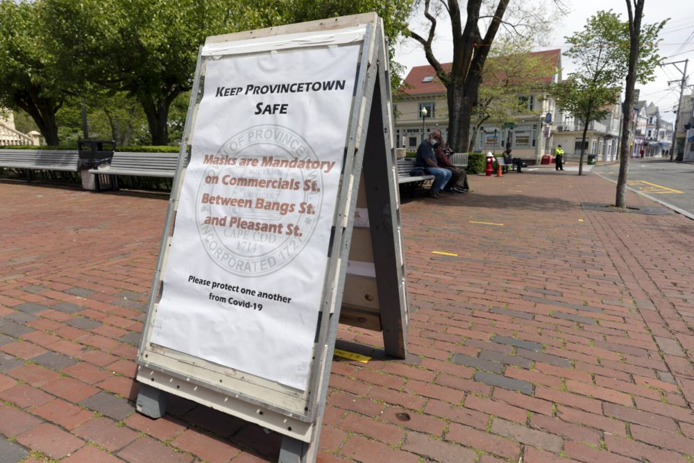 A sign advises that protective masks are required on the usually busy Commercial Street, May 25, 2020, in Provincetown, Mass. (Michael Dwyer/ AP)