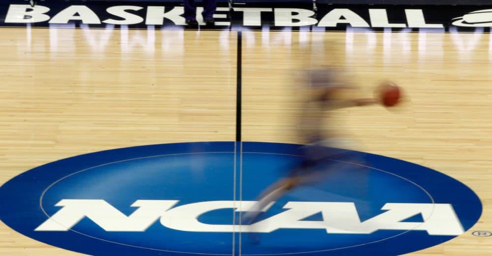 A player runs across the NCAA logo (Keith Srakocic/AP)