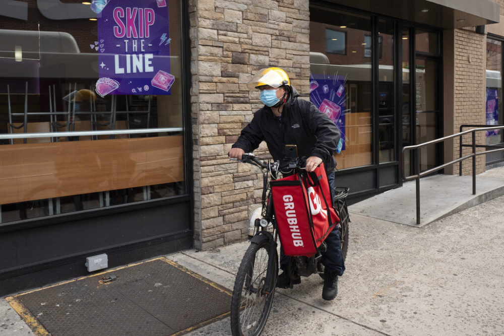 A delivery man bikes with a food bag from Grubhub. (Mark Lennihan/AP)