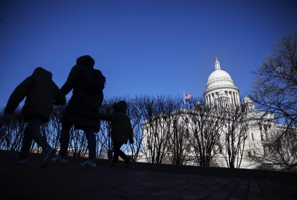 Pedestrians walk past the Rhode Island Statehouse. (David Goldman/AP)