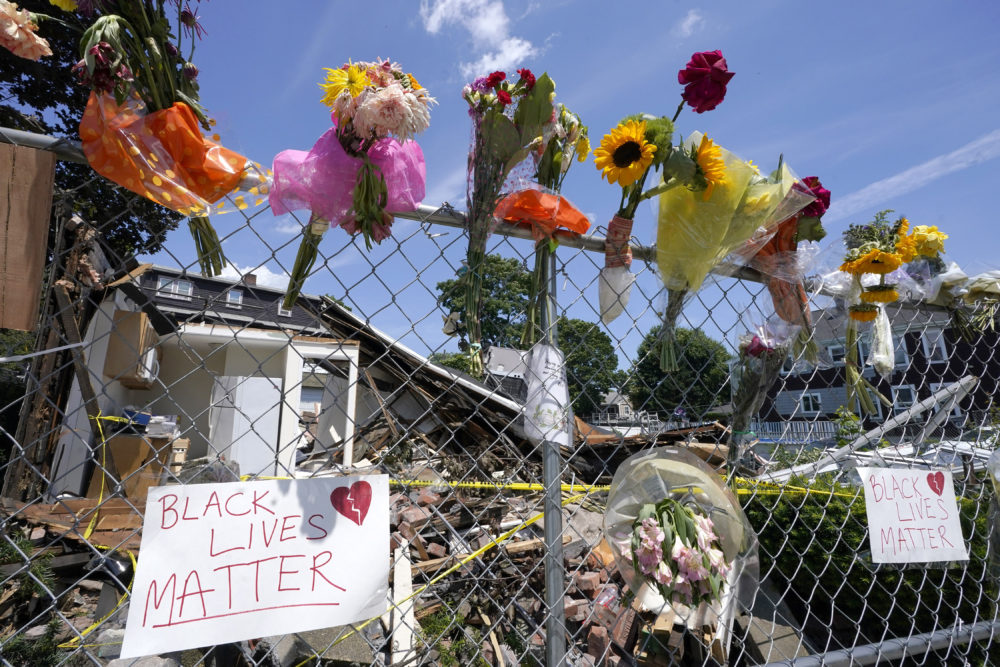 Signs and flowers are attached to a fence outside a building in Winthrop, Mass., on Monday, June 28, 2021, where an armed man crashed a hijacked truck, Saturday, June 26, 2021, then fatally shot two people before being killed by police. (Steven Senne/AP)