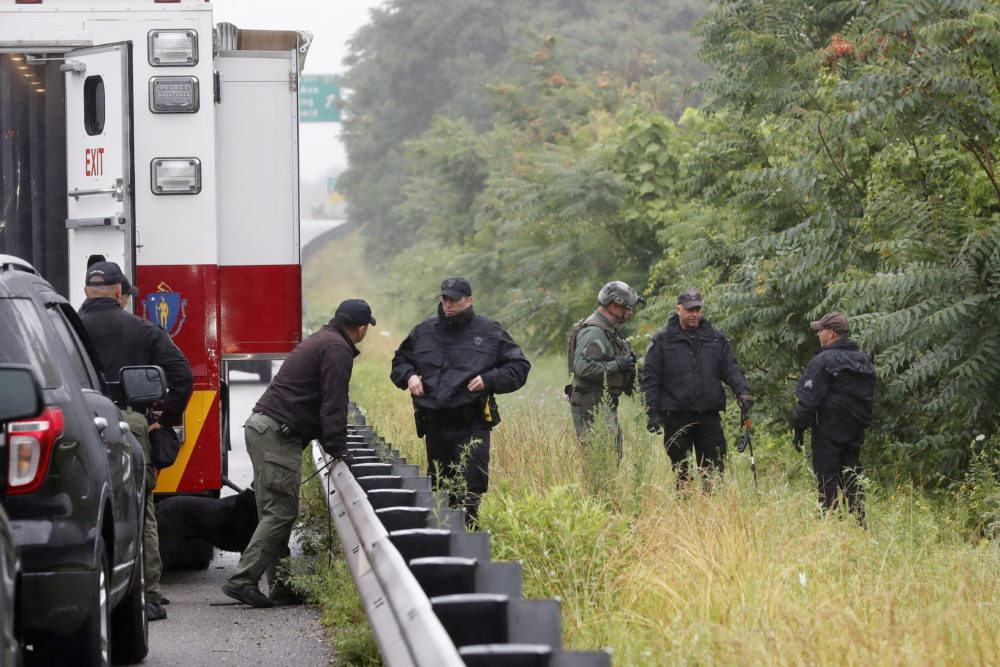 Police work in the area of an hours long standoff with a group of armed men that partially shut down I-95 on Saturday in Wakefield, Mass. (Michael Dwyer/AP)