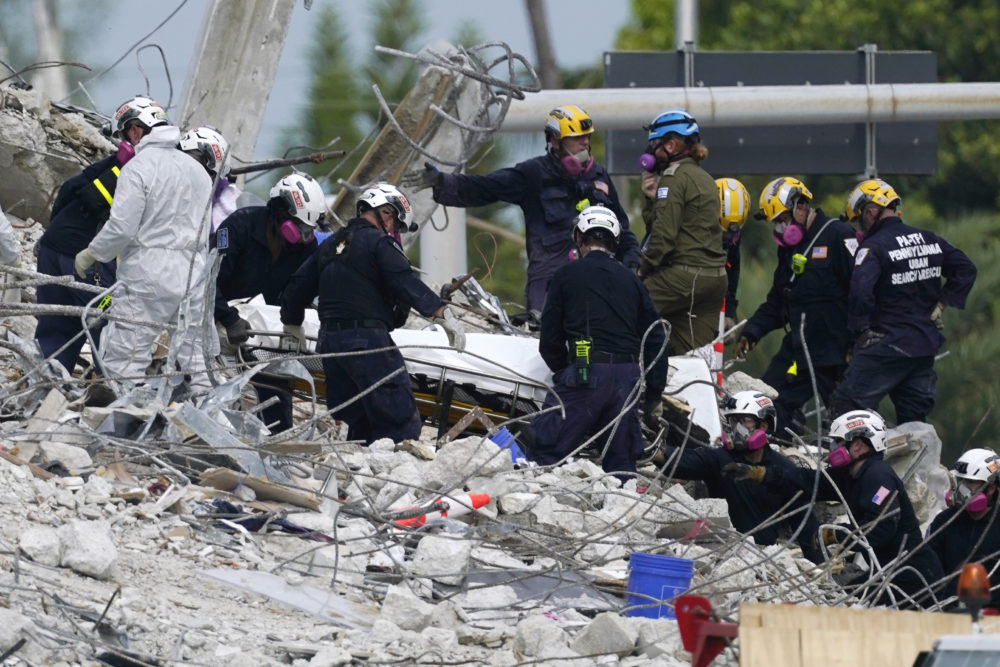 Monday, July 5, 2021: Rescue workers move a stretcher containing recovered remains at the site of the collapsed Champlain Towers South condo building, in Surfside, Fla. (Lynne Sladky/AP)